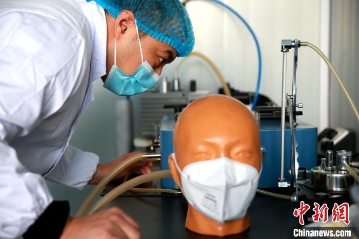 车间检测中心工作人员正在对生产口罩进行抽检,保证口罩质量。 梁犇 摄