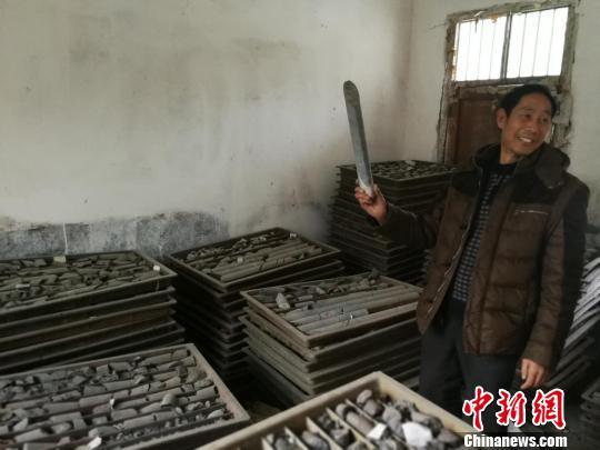 图为程立芳展示石墨矿藏探井勘探样品。 王祎 摄