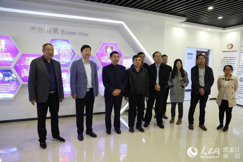 七台河市市长贾君与北京大学院士刘忠范观看宝泰隆发展历程。