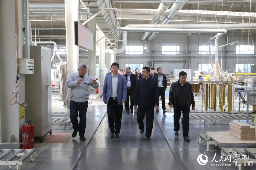 七台河市市长贾君与北京大学院士刘忠范调研双叶家具智能制造生产流水线。